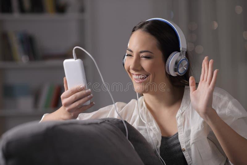 Счастливая женщина имея видео- звонок в ночи на кресле стоковое фото