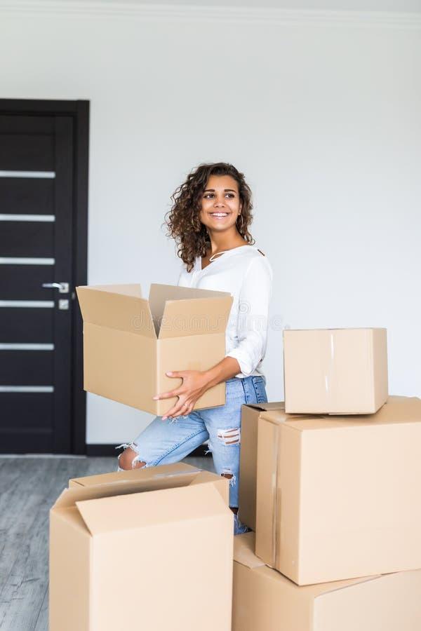 Счастливая женщина двигая в коробки нося коробок Аранжировать маленькой девочки внутренний и распаковывать на новом доме многоква стоковая фотография