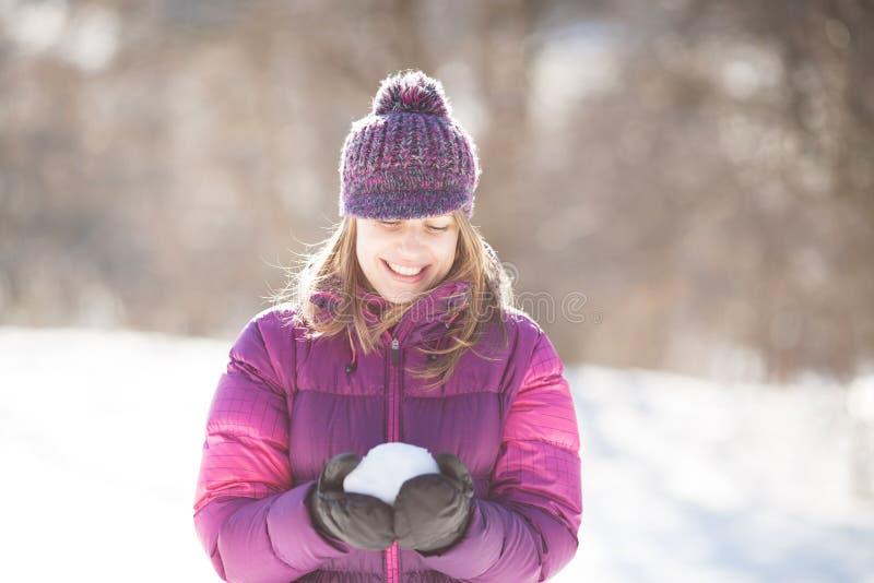 Счастливая женщина держа снег в руках стоковые изображения