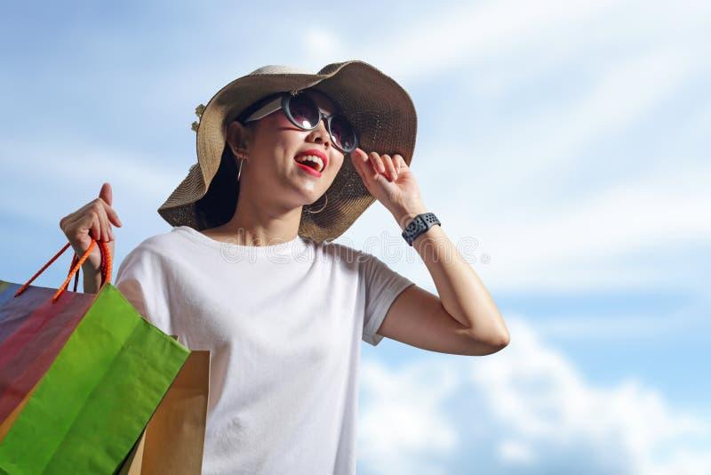 Счастливая женщина с хозяйственными сумками наслаждаясь в покупках Концепция образа жизни стоковые фотографии rf
