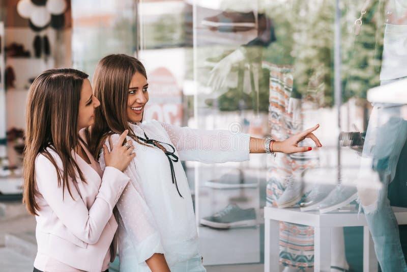 Счастливая женщина указывая палец в окне магазина стоковые фотографии rf