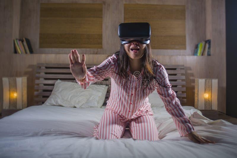 Счастливая и возбужденная женщина играя с прибором шлемофона изумленных взглядов виртуальной реальности VR имея потеху на кровати стоковая фотография