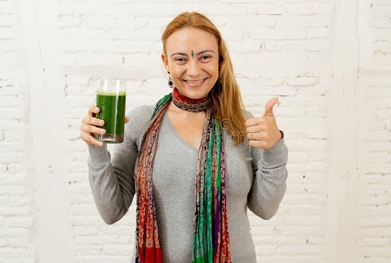 Счастливая красивая женщина усмехаясь и выпивая здоровый smoothie свежего овоща в здоровом образе жизни стоковое изображение