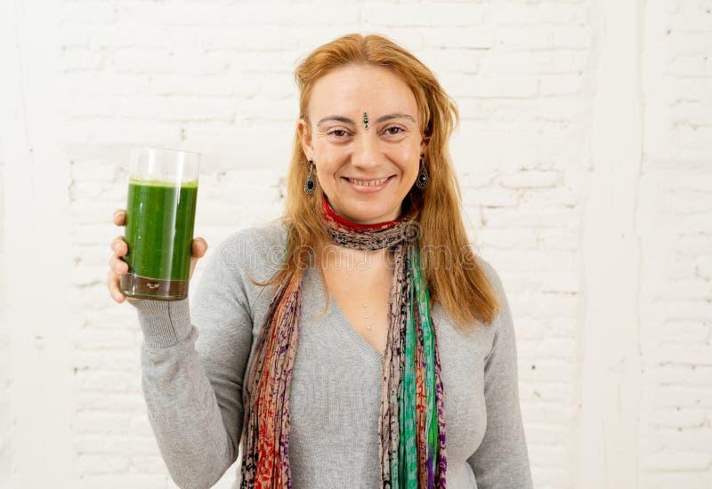 Счастливая красивая женщина усмехаясь и выпивая здоровый smoothie свежего овоща в здоровом образе жизни стоковое фото rf