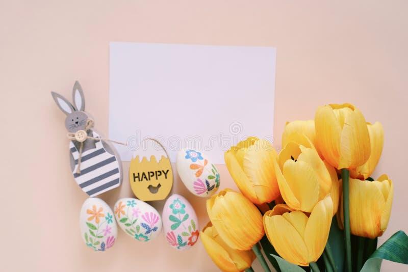 Счастливая концепция пасхи с пустой картой, деревянным зайчиком, красочными пасхальными яйцами и желтыми тюльпанами стоковые изображения rf
