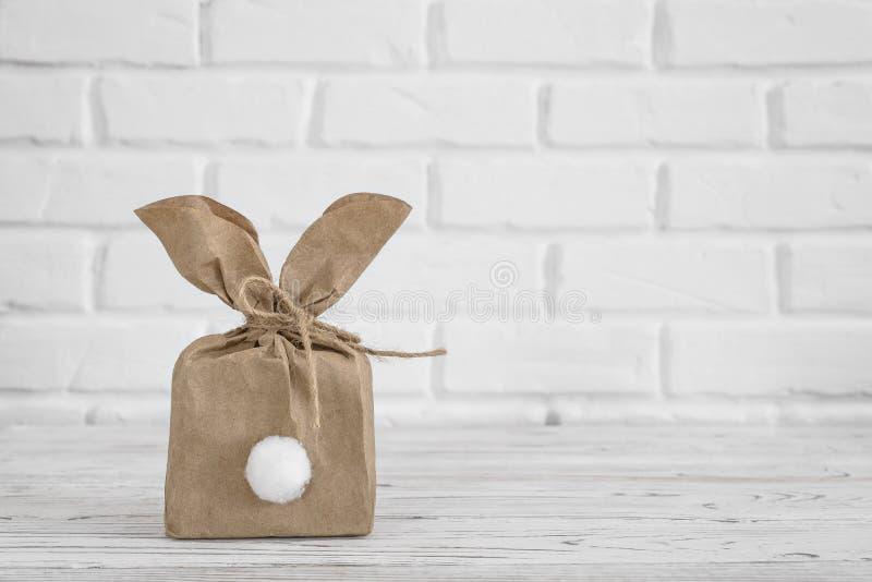 Счастливая концепция предпосылки пасхи Плоский положенный бумажный мешок минимализма такие же зайчик или кролик для подарка или н стоковое фото