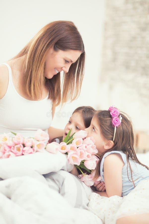 Счастливая концепция дня ` s матери Мама с близнецами дочерей twocute молодыми на кровати в спальне и букете тюльпанов цветков стоковая фотография