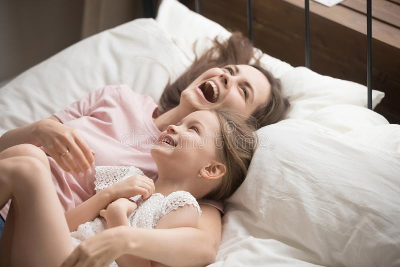 Счастливая мать семьи обнимая лежать дочери ребенк смеясь на кровати стоковые фотографии rf