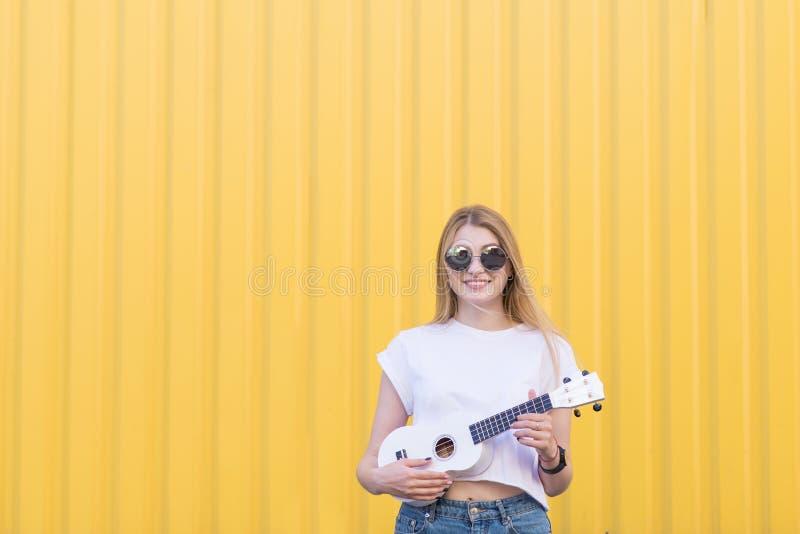 Счастливая, милая девушка играет гавайскую гитару на фоне желтой стены и улыбок Музыкальная принципиальная схема стоковое изображение