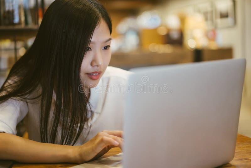 Счастливая молодая азиатская девушка работая на кофейне с ноутбуком стоковое изображение