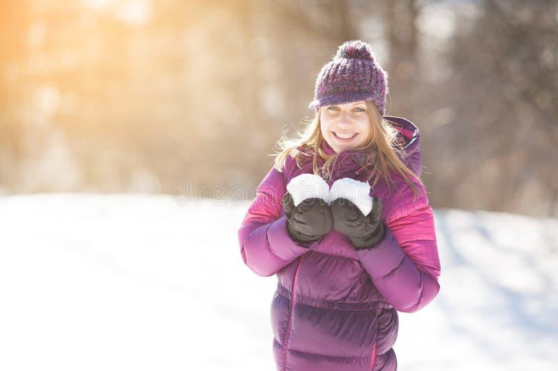 Счастливая молодая женщина держа 2 снежного кома стоковое фото rf