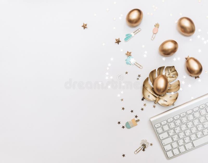 Счастливая пасха! Стильная предпосылка канцелярских принадлежностей с яйцами золота на белой предпосылке стоковые изображения