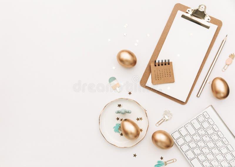 Счастливая пасха! Стильная предпосылка канцелярских принадлежностей с яйцами золота на белой предпосылке стоковые фотографии rf