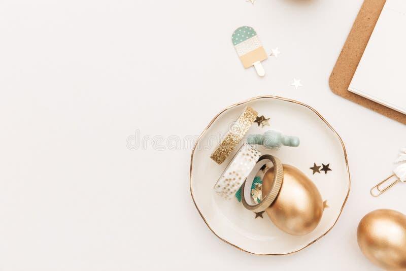 Счастливая пасха! Стильная предпосылка канцелярских принадлежностей с яйцами золота на белой предпосылке стоковое изображение rf