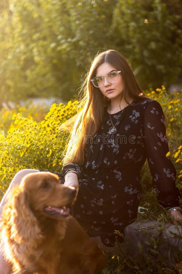 Счастливая девушка играя с красной собакой на зеленой траве в природном парке outdoors, красивой молодой женщине и друзьях собаки стоковое фото