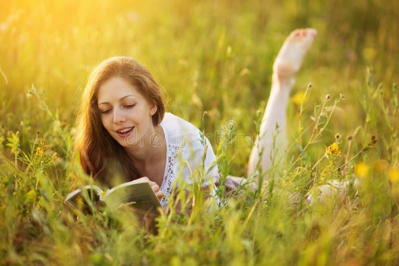 Счастливая девушка лежащ и читающ книгу стоковое фото rf