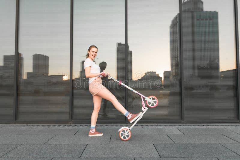 Счастливая девушка спорт в белых футболке и кабеле делает фокус на розовом ветроуловителе на темной предпосылке стоковое изображение rf