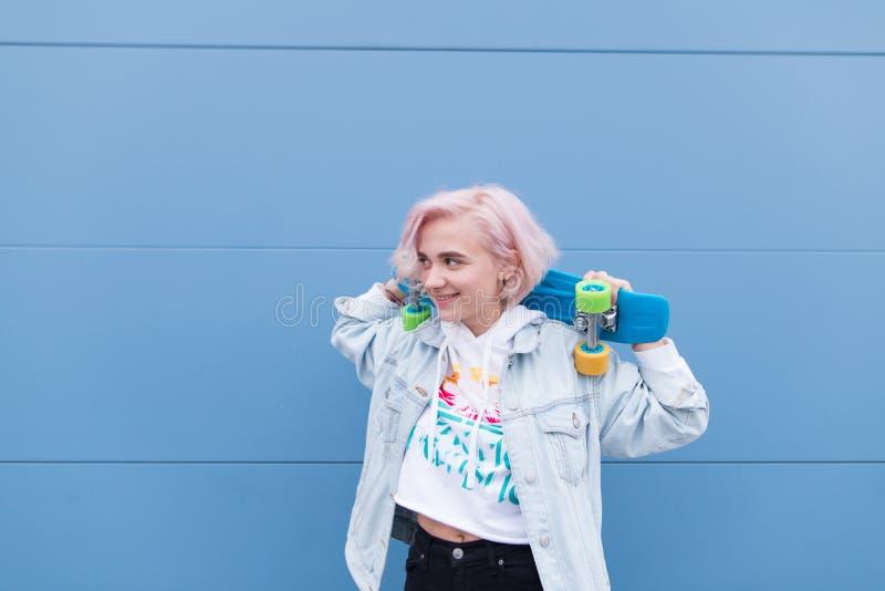 Счастливая девушка стоит со скейтбордом на фоне голубой стены и улыбок стоковое фото