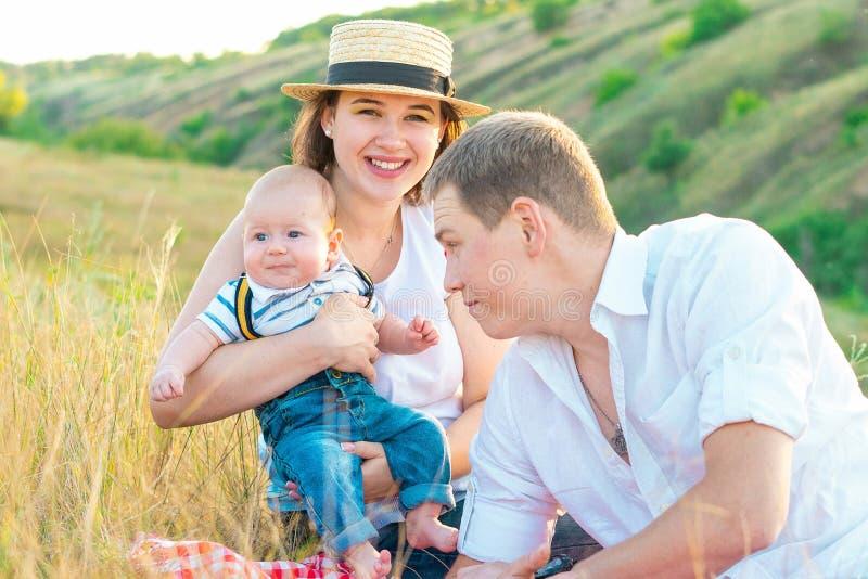 Счастливая семья тратя время совместно на заходе солнца стоковые изображения