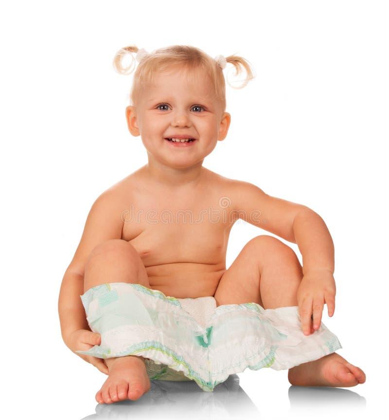 Счастливая смеясь маленькая девочка с устранимой пеленкой изолированной на белизне стоковое фото rf