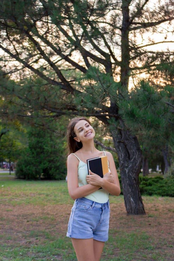 Счастливая студентка держит книгу и мечтает о том, что-то Милая женщина усмехающся и идущ в парк стоковая фотография