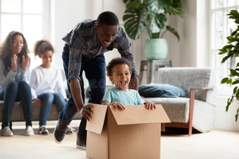 Счастливая черная игра семьи с детьми двигая к новому дому стоковые фотографии rf
