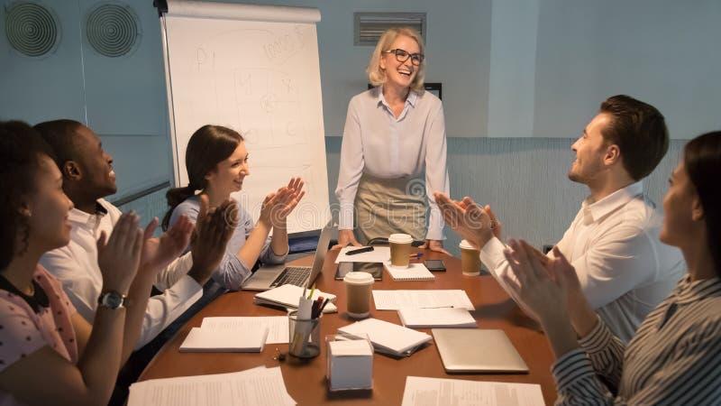 Счастливая разнообразная команда зааплодировать благодарит счастливого тренера ментора для представления стоковые фото