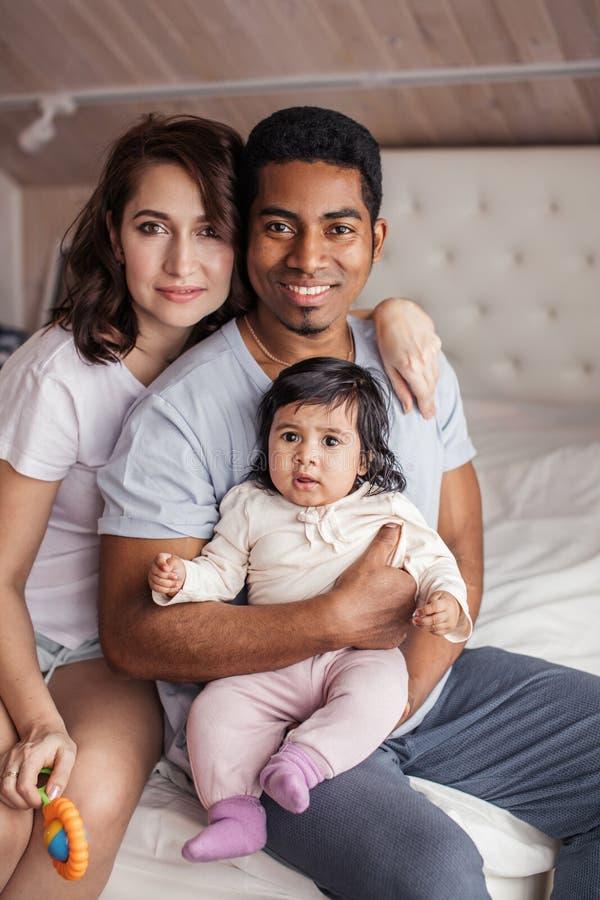 Счастливая разнообразная семья смотря камеру внутри помещения стоковые изображения rf