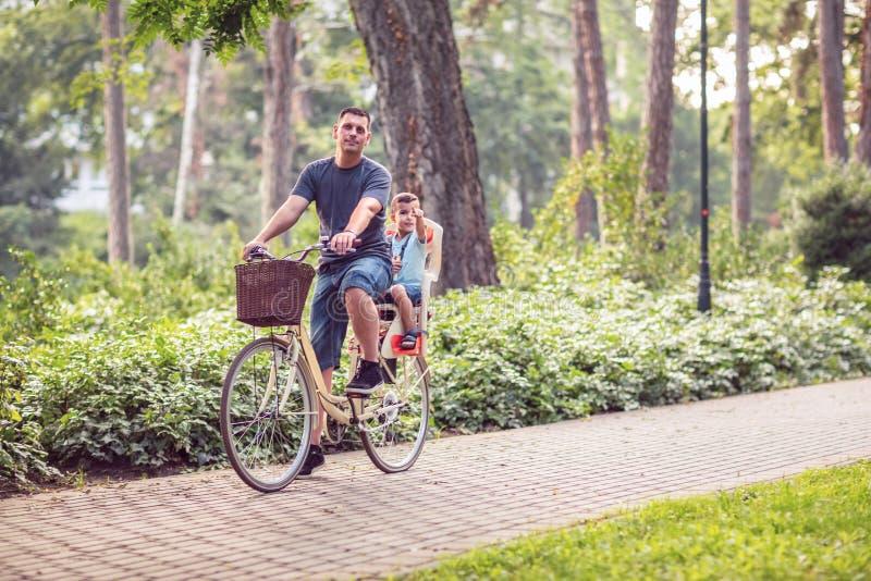 Счастливые велосипеды папы и сына ехать outdoors в парке города стоковая фотография