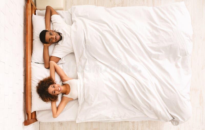 Счастливые женатые черные пары отдыхая в кровати стоковые фотографии rf