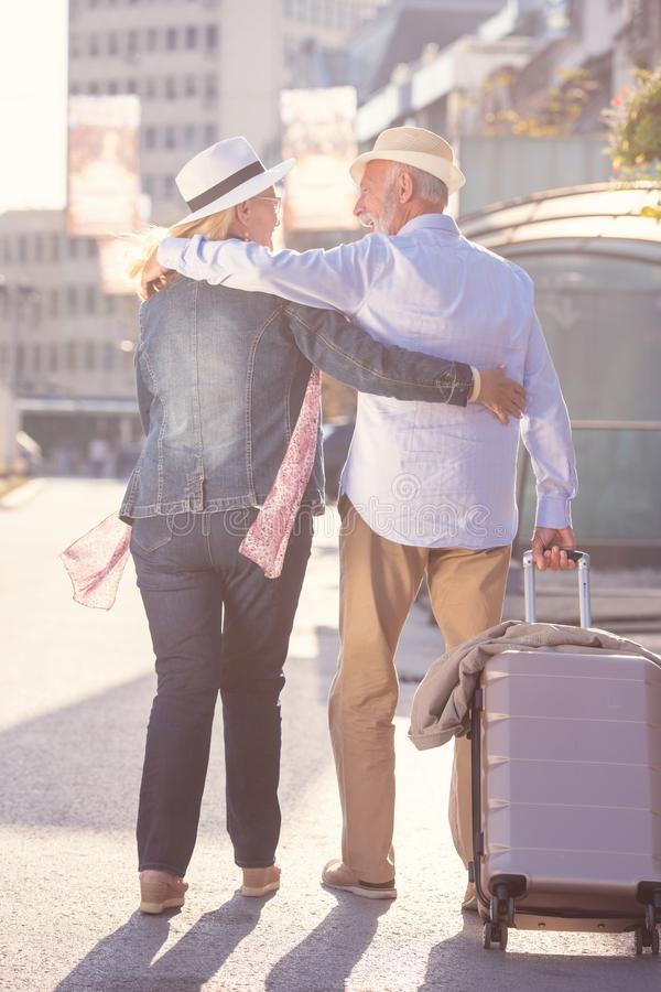 Счастливые жизнерадостные старшие пары туристов с проводником карты и города идя на улицу стоковая фотография
