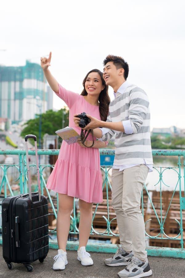 Счастливые молодые пары путешественников держа карту в руках стоковая фотография rf