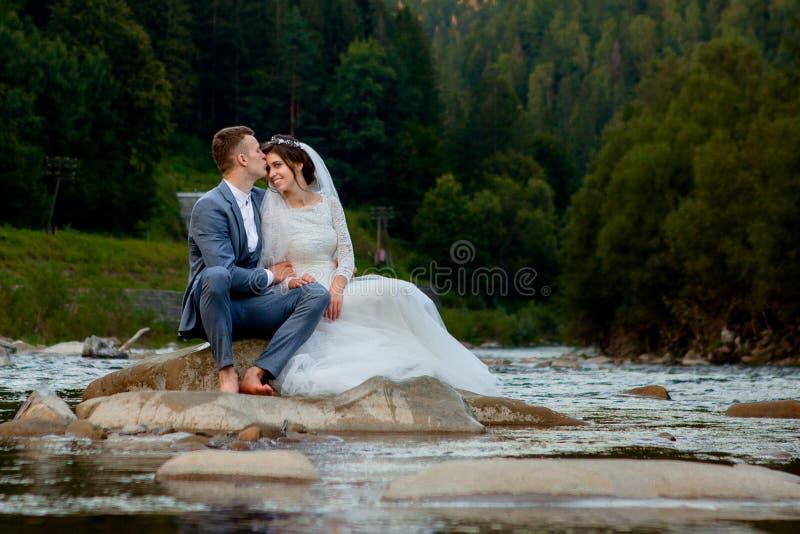 Счастливые новобрачные стоя и усмехаясь на реке Honeymooners, фото на день Валентайн стоковая фотография