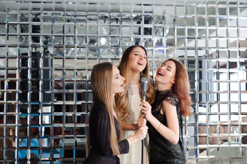 Счастливые девушки имея потеху поя на партии стоковая фотография rf