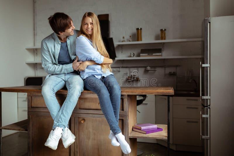 Счастливые усмехаясь молодые пары в голубой ткани джинсовой ткани сидя в кухне стоковая фотография rf