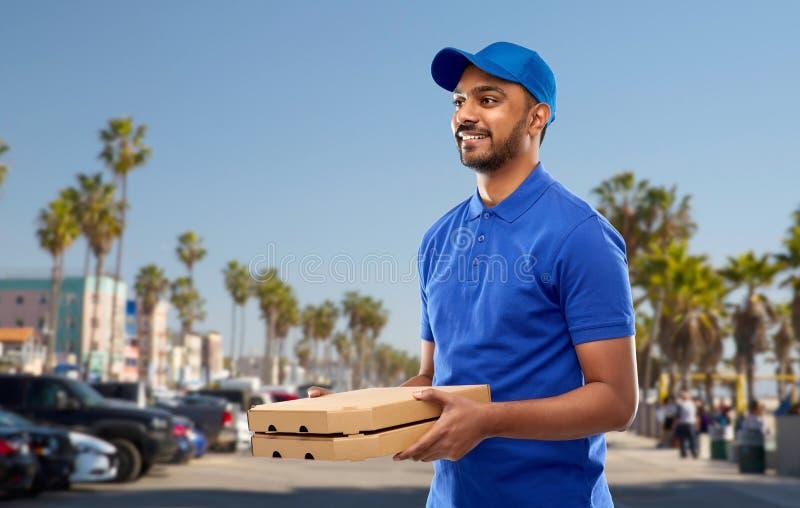 Счастливый индийский работник доставляющий покупки на дом с коробками пиццы в сини стоковые изображения
