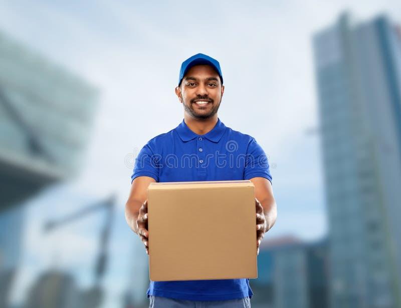Счастливый индийский работник доставляющий покупки на дом с коробкой пакета в сини стоковая фотография rf