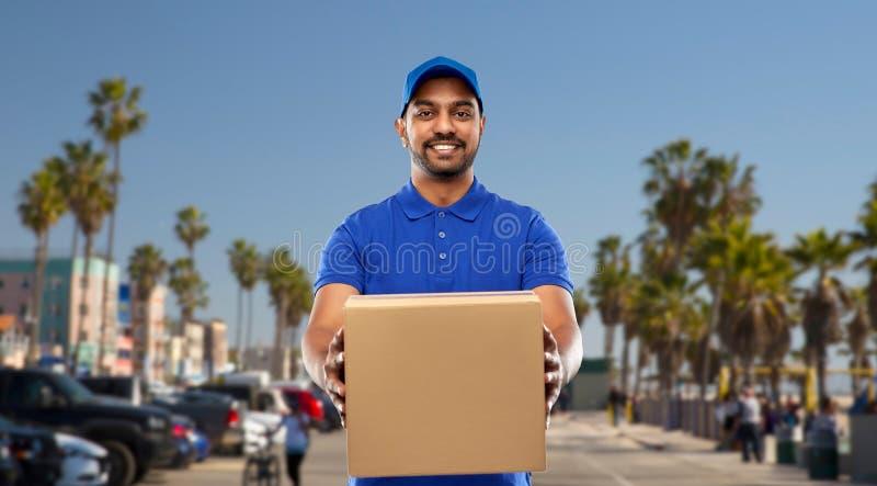 Счастливый индийский работник доставляющий покупки на дом с коробкой пакета в сини стоковое изображение rf