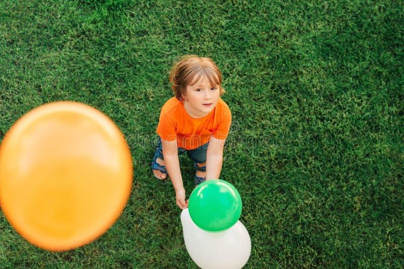 Счастливый мальчик 4-5 лет старой игры с красочными воздушными шарами стоковая фотография rf