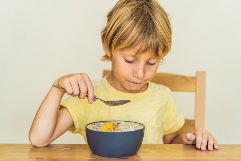 Счастливый мальчик сидя и есть свежий шар smoothie с манго, плодом дракона, granola и семенами chia стоковое изображение rf