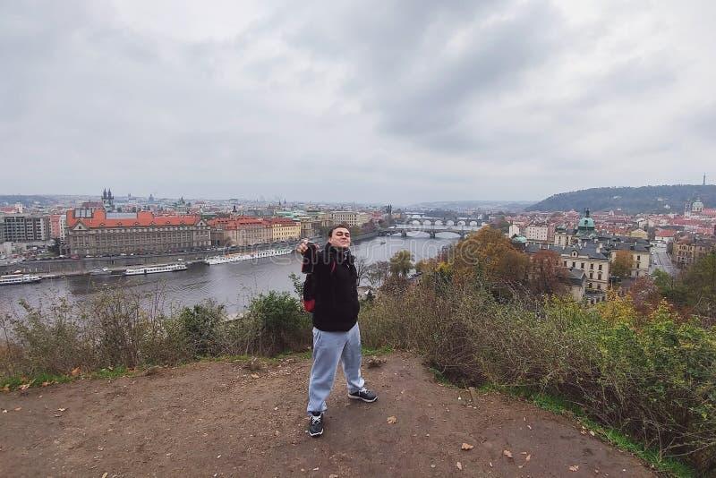 Счастливый мужской турист предлагает консервную банку пива к другу на фоне панорамы чехословакской столицы Праги стоковые фото