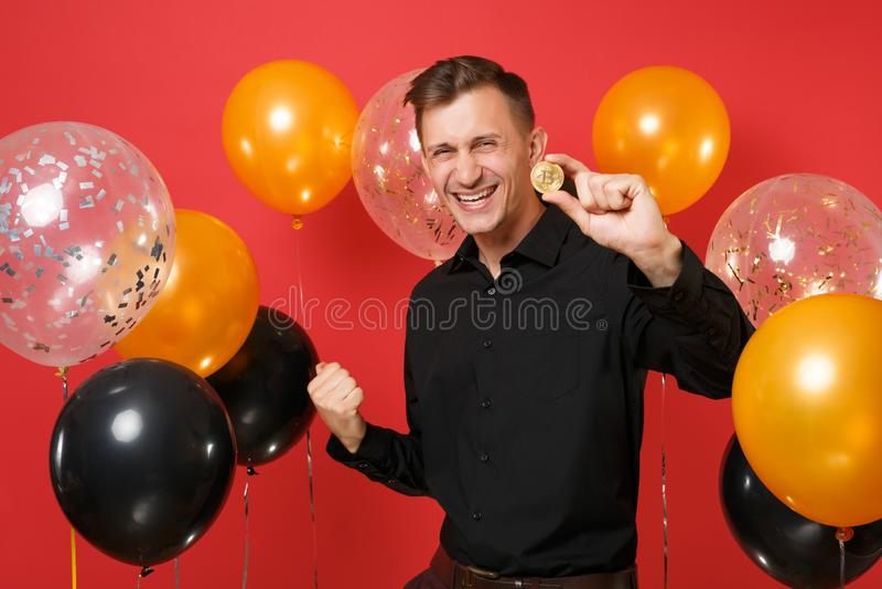 Счастливый молодой человек в классической рубашке делая жест победителя держа bitcoin, монетку металла золотого цвета, будущей ва стоковые изображения