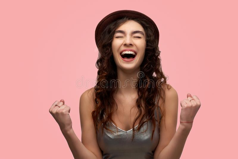 Счастливый победитель женщины обхватывая ее кулаки и выкрикивая да с ободрением, празднующ, достигающ целей стоковые изображения