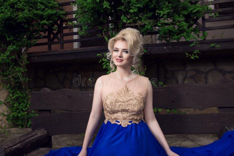 Счастливый, усмехающся, красивая белокурая женщина в элегантном платье стоковые изображения