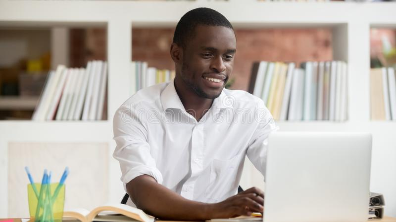 Счастливый черный студент используя приложения изучает онлайн на компьютере стоковое изображение