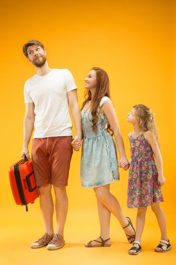 Счастливый родитель с дочерью и чемоданом на студии изолированной на желтой предпосылке стоковое фото rf