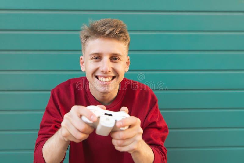 Счастливый gamer с gamepad в его руках играет консоль на предпосылке и взглядах бирюзы на камере стоковое изображение rf