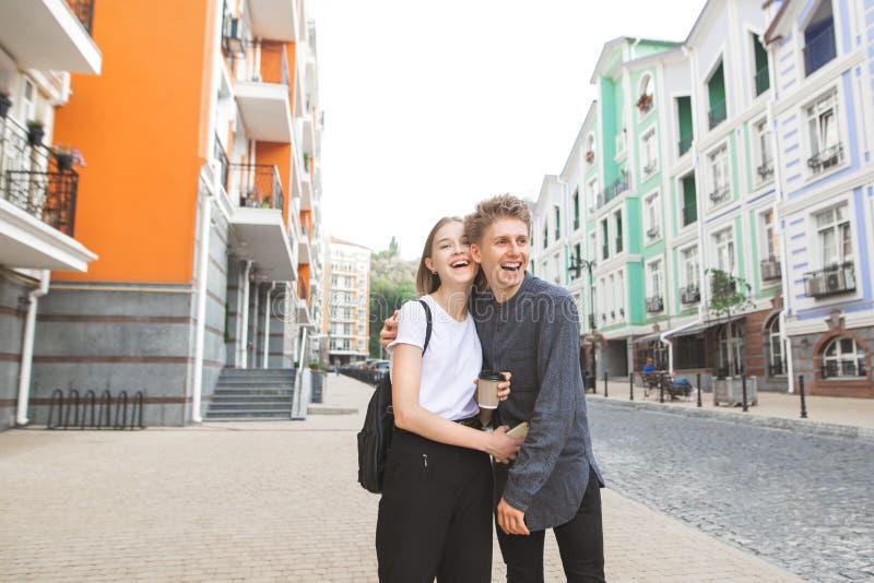 Счастливое молодое положение пар на улице, усмехаясь и обнимая Любя молодые пары идя, обнимая и усмехаясь стоковые фото