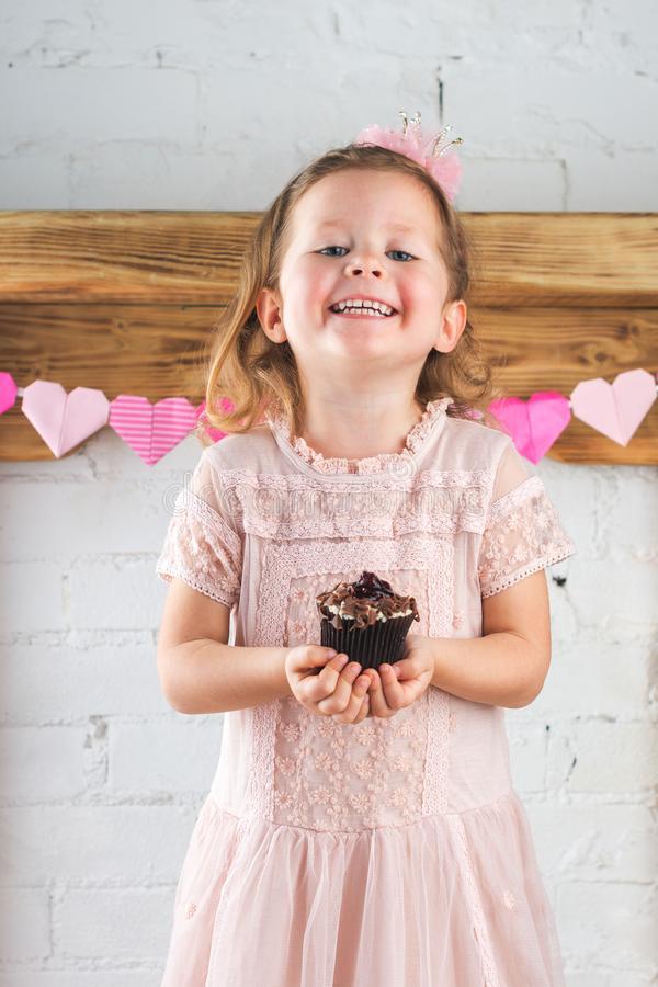 Счастливое пирожное удерживания маленькой девочки стоковое фото rf