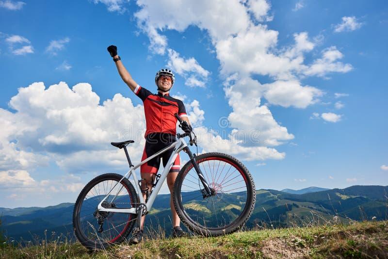 Счастливое профессиональное положение велосипедиста спортсмена с велосипедом на холме, rasing рукой по пересеченной местностей стоковые фотографии rf